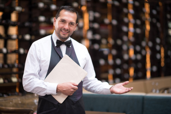 Friendly elegant waiter welcoming people to a restaurant - © istock.com/andresr